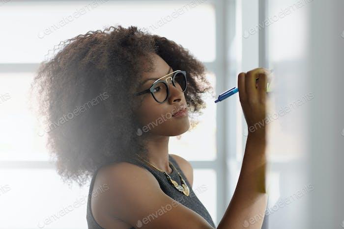 Porträt einer lächelnden Geschäftsfrau mit einem Afro in hellen Glas Büro