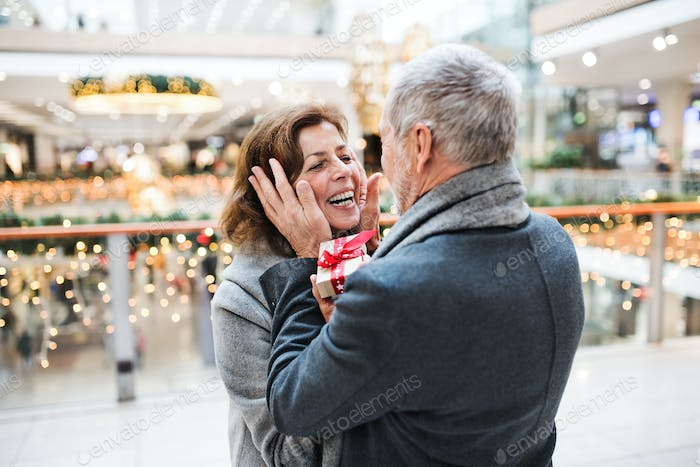A senior man giving a present to a woman at shopping center at Christmas time.