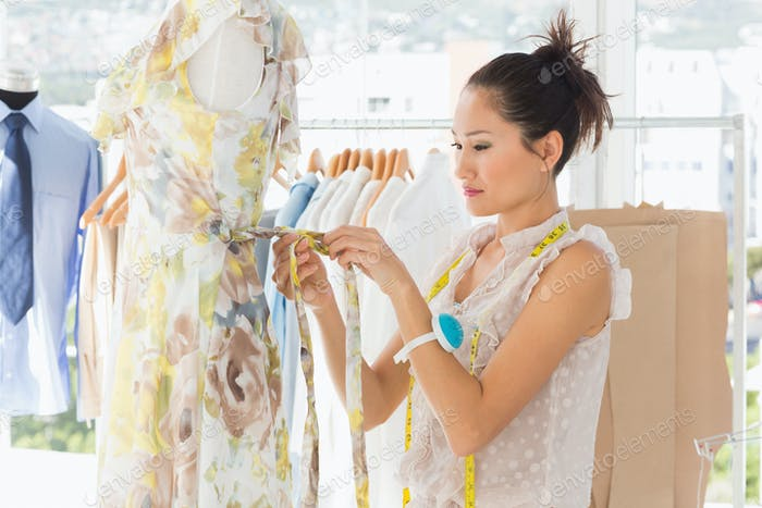 Side view of a beautiful female fashion designer working on dress at the studio