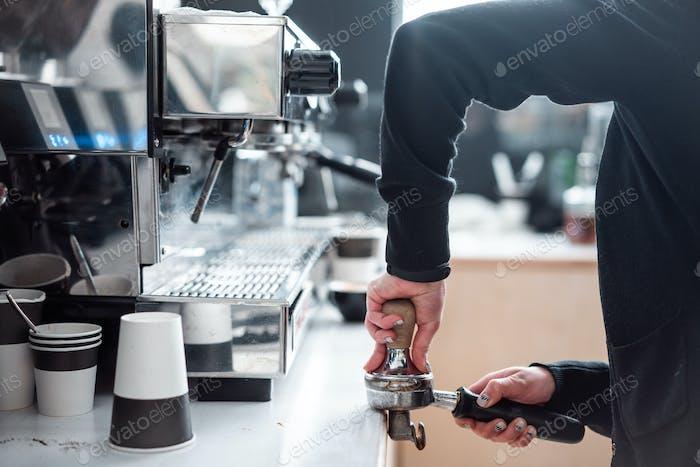 Barista presst gemahlenen Kaffee mit Tamper.