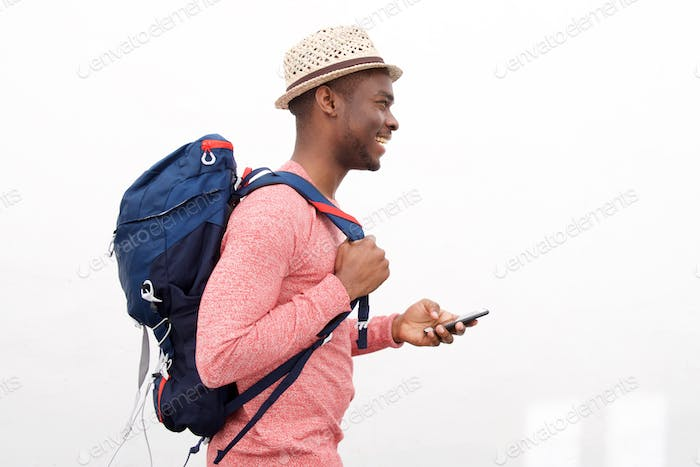 handsome young african american man smiling with cellphone and bag against white background