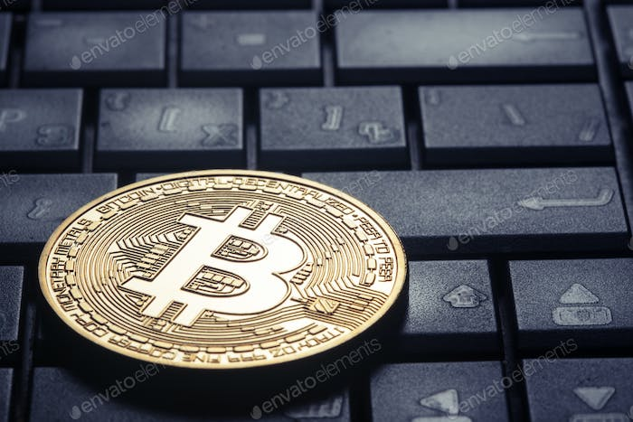 Golden bitcoin on the computer keyboard