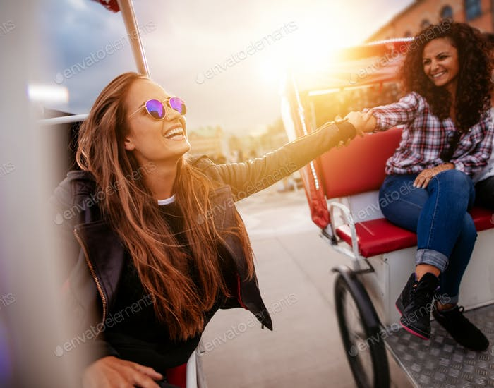 Young women having fun on two tricycles