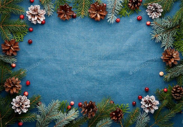 Weihnachten und Happy New Year dunkelblauen Hintergrund. Rahmen mit Tannenzweigen, Zapfen