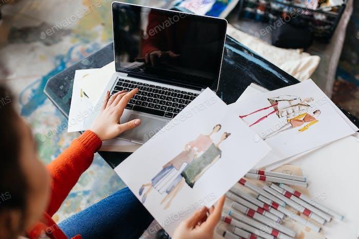 Draufsicht der jungen Frau sitzt am Tisch arbeiten auf Laptop w