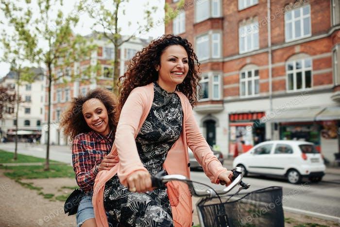 Jóvenes Amigos Alegre montando una bicicleta en la Ciudad