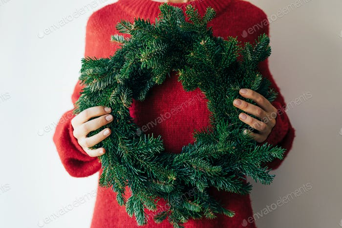 A woman is holding a fir natural Christmas wreath. Christmas minimal celebration concept.