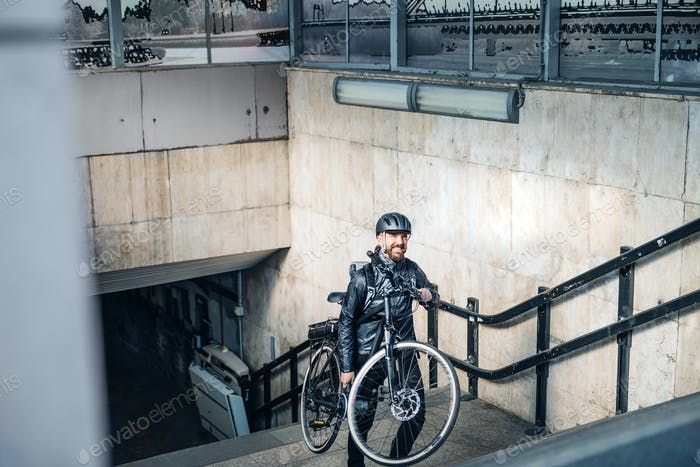 Male courier delivering packages in city, carrying bicycle up the stairs.