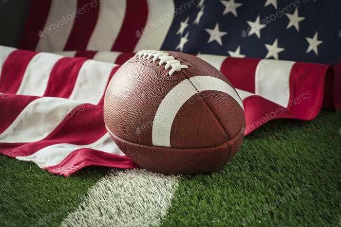 Football and American flag on green field