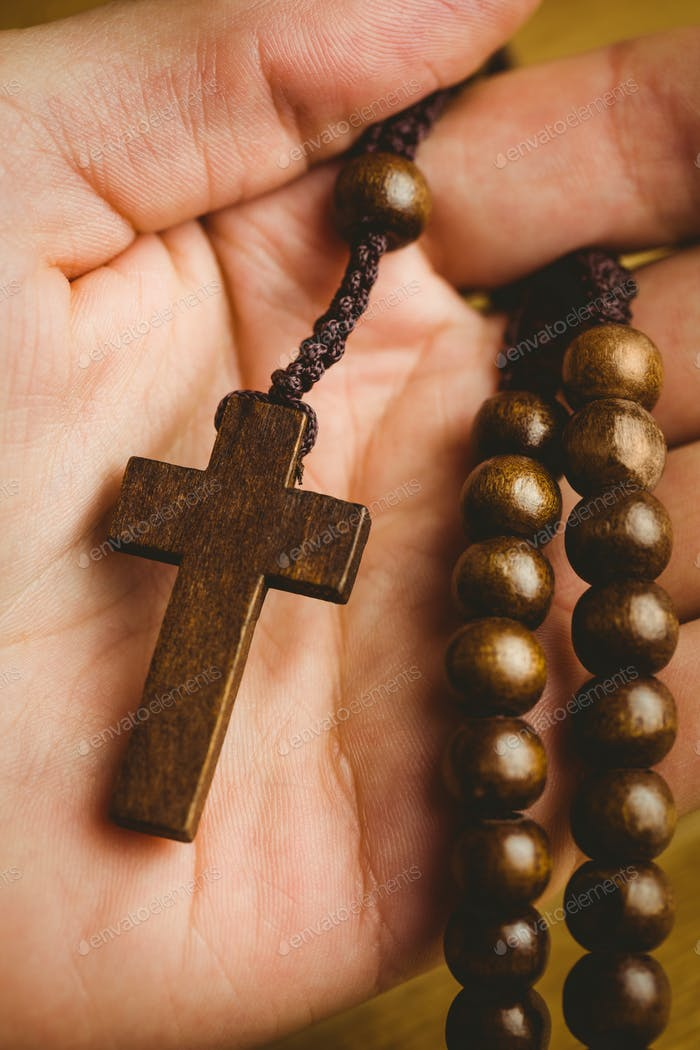 Hand holding wooden rosary beads overhead shot