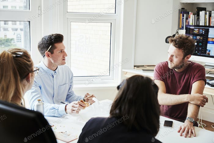 Four people at a business meeting around a table.