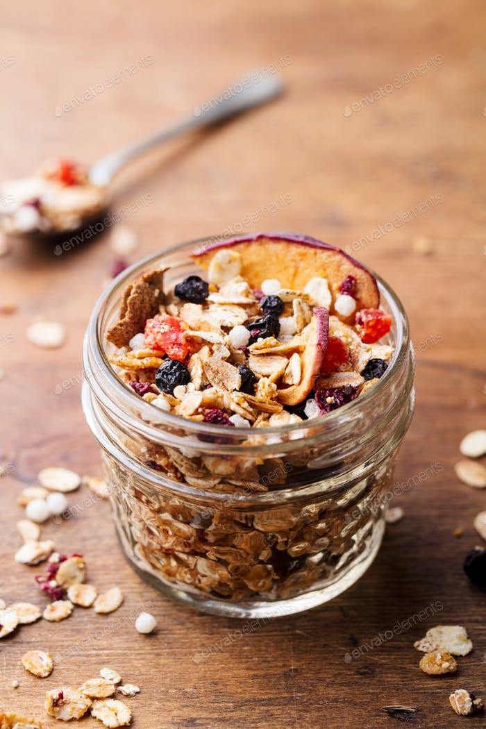 Granola, Muesli in Glass Jar. Healthy Breakfast. Organic Oats with Apples, Berries and Nuts.