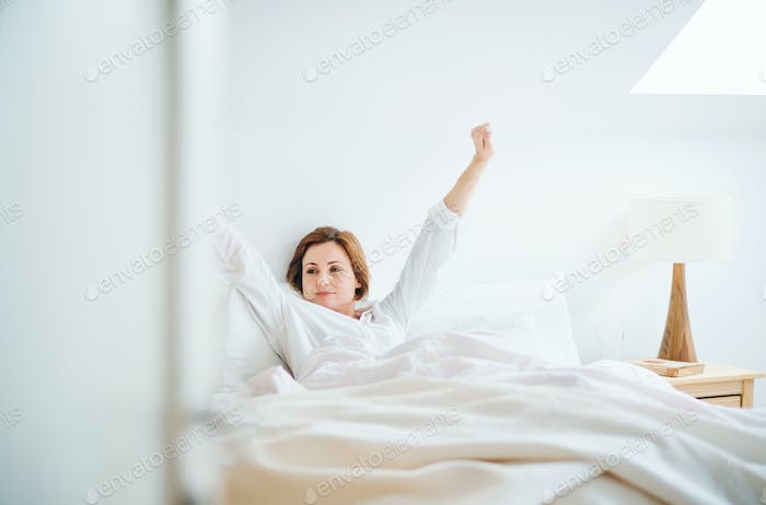 A young woman sitting in bed indoors in the morning in a bedroom, stretching.