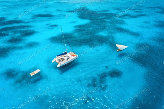 Aerial view of the yacht and sailboat in clear blue sea at sunset