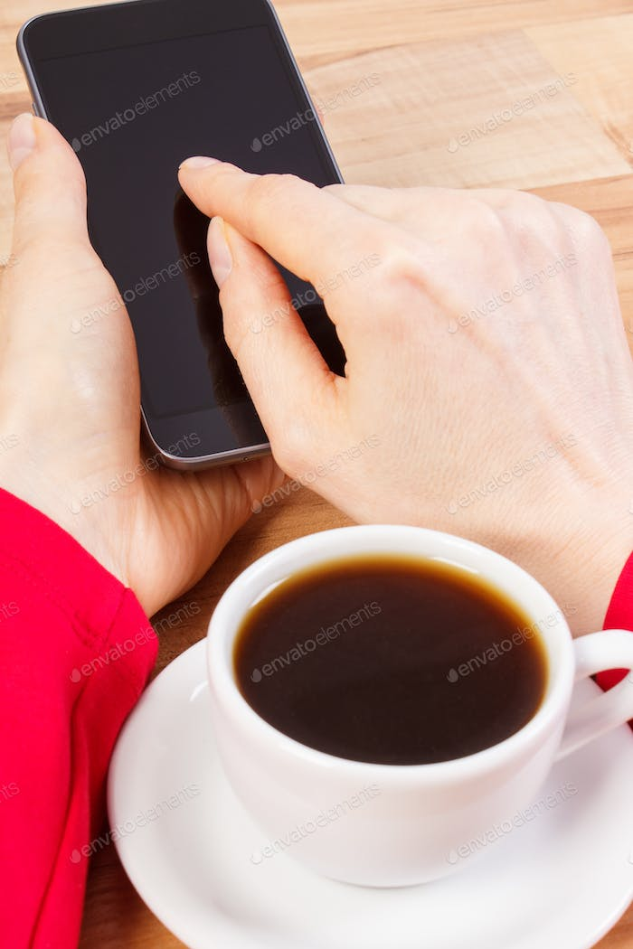 Hand of woman touching blank screen of mobile phone, relax with cup of coffee