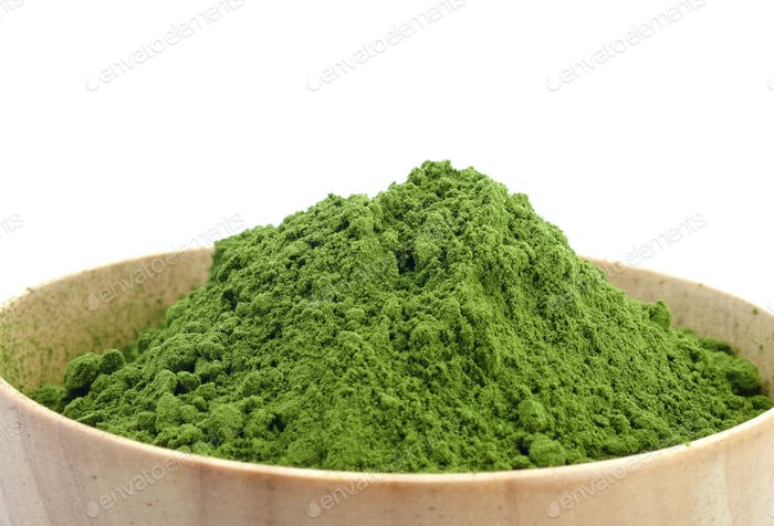 Green tea powder in wood bowl on white background.