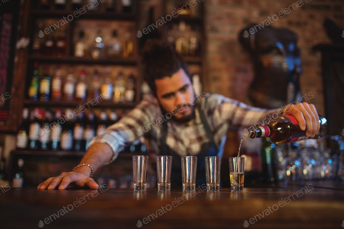 Waiter pouring tequila into shot glasses at counter