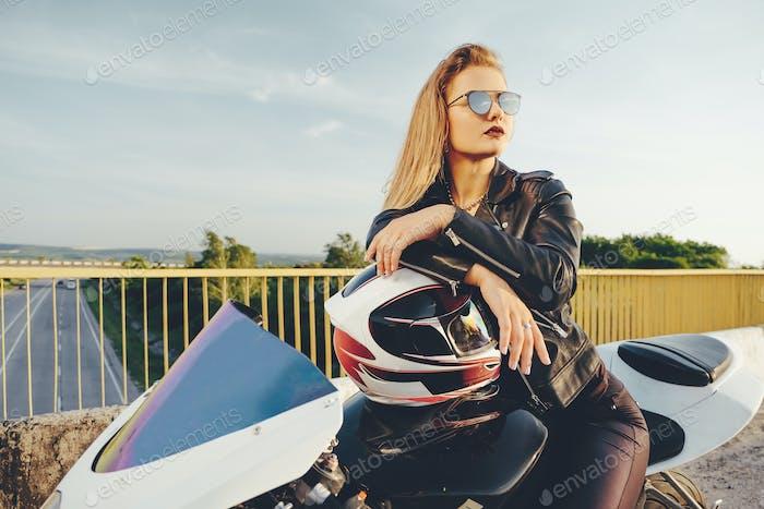 Beautiful woman with sunglasses driving on motorbike