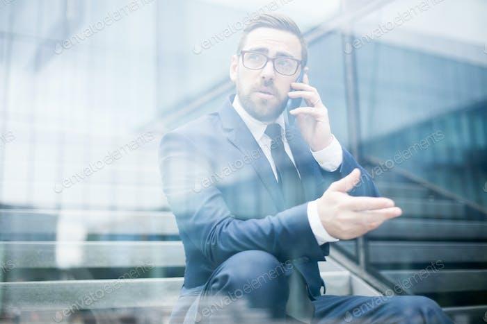 Business man sitting on steps talking smartphone