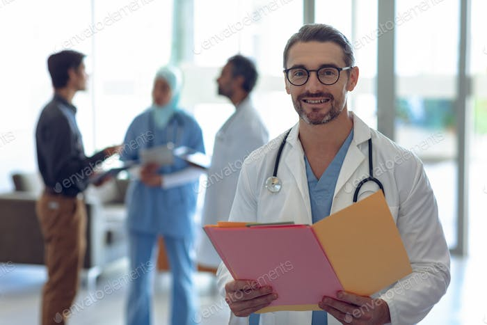 Happy Caucasian male doctor holding medical file and looking at camera in hospital.