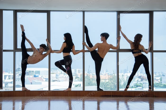 Dancers stretching at big window