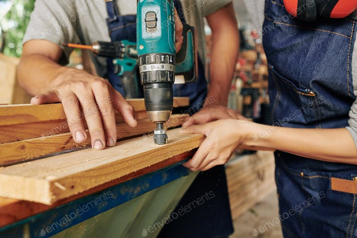 Carpenters drilling holes in wood