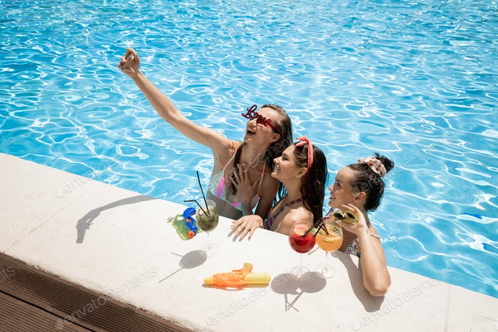 Tree stylish young girls in the swimsuits are relaxing and making salfie with cocktails in the