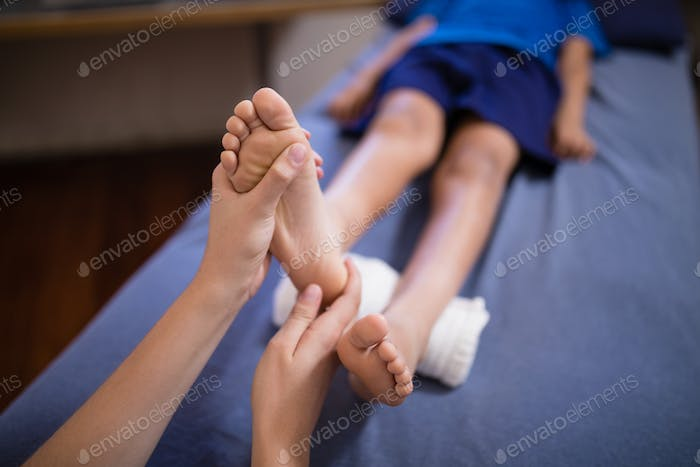 High angle view of boy lying on bed receiving foot massage from female therapist