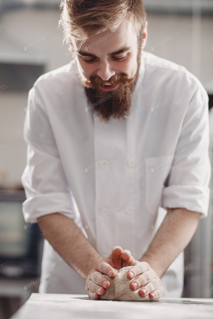 Charismatic baker with a beard and mustache kneads dough on the table in the bakery