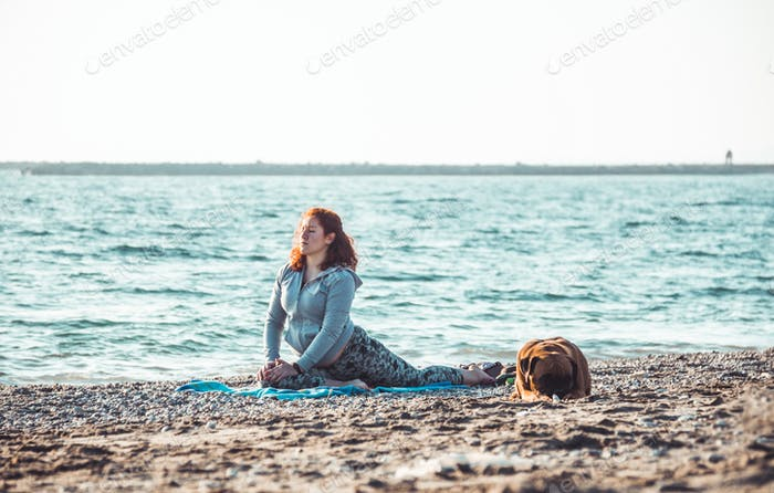 girl doing yoga and stretching on the beach