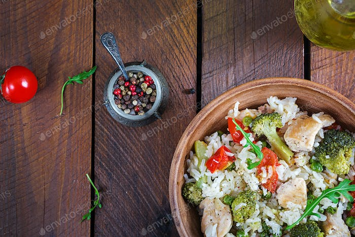Delicious chicken, broccoli, green peas, tomato stir fry with rice.