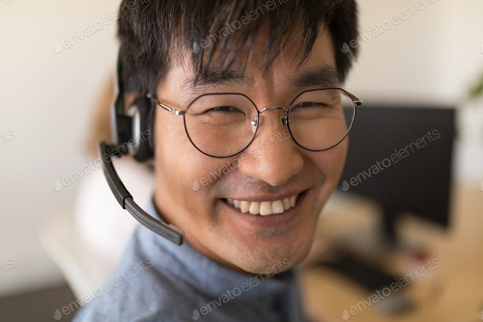 Portrait of happy Asian male executive in headset smiling in office. He wears glasses