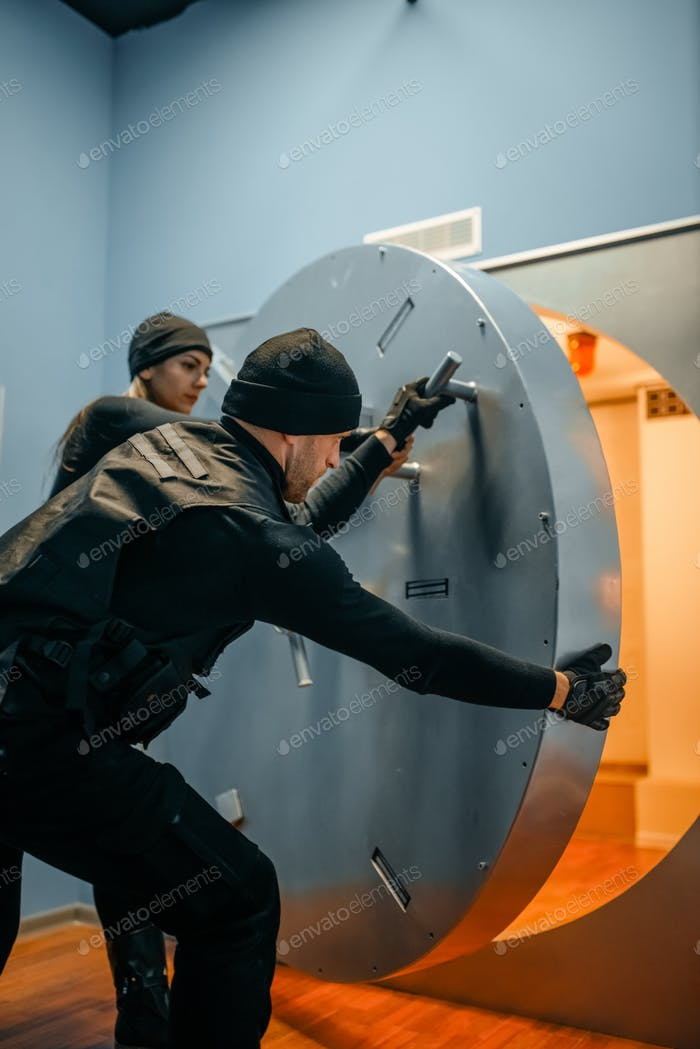 Robbers in black uniform opening vault door