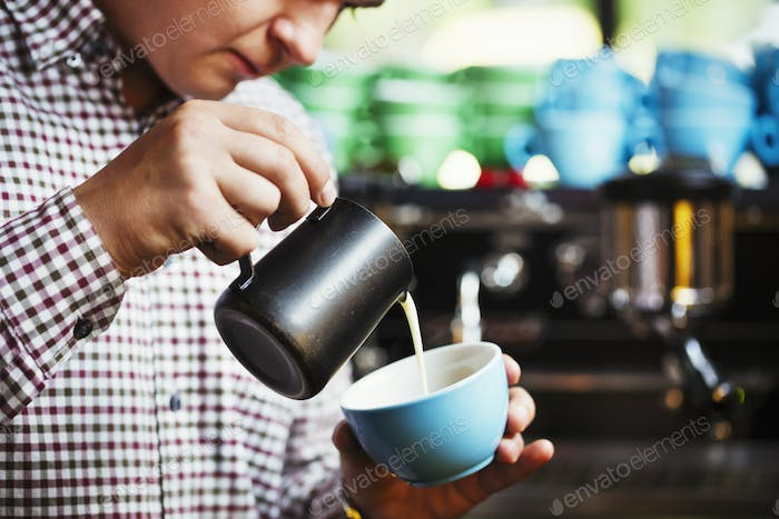 Specialist coffee shop. A man pouring hot milk into a cup of coffee to make a pattern on the top.