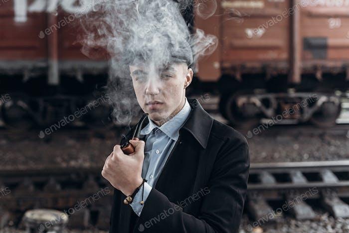 Стильный гангстер курение в твид, позируя на фоне железной дороги