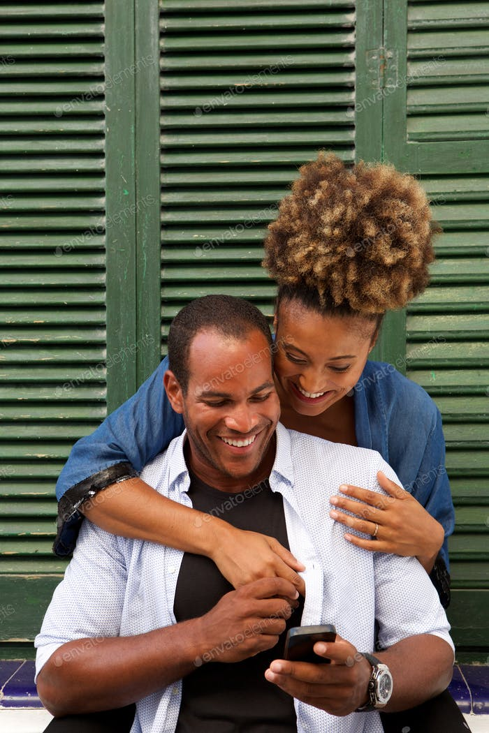Happy couple in embrace with man holding mobile phone
