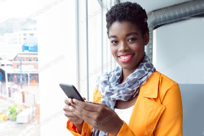 Portrait of African-american Businesswoman using mobile phone near window in office
