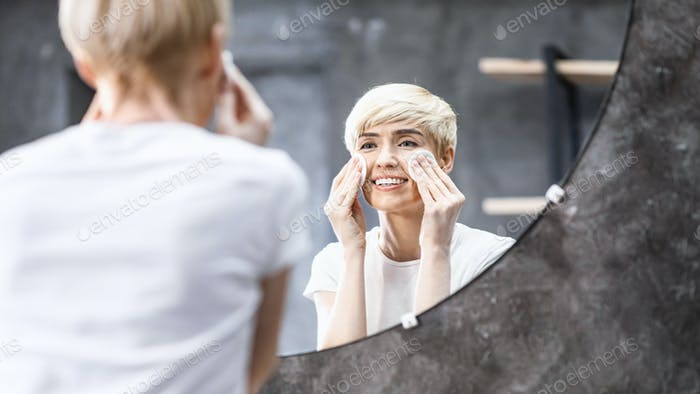 Lady Removing Makeup Using Cotton Pads In Bathroom At Home