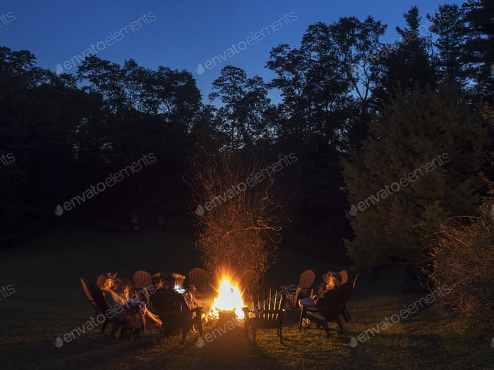 A group of people seated around a campfire at dusk.