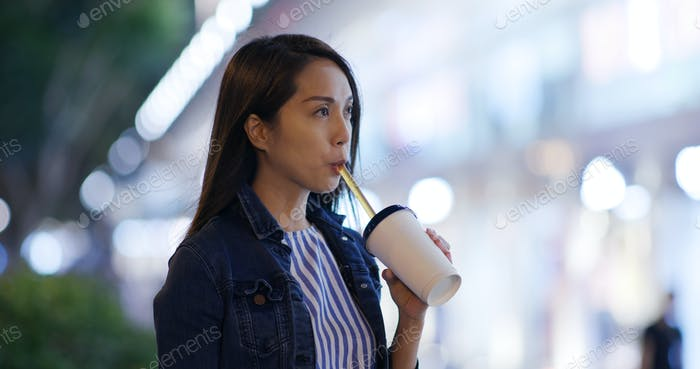 Woman drink of tea at city in evening
