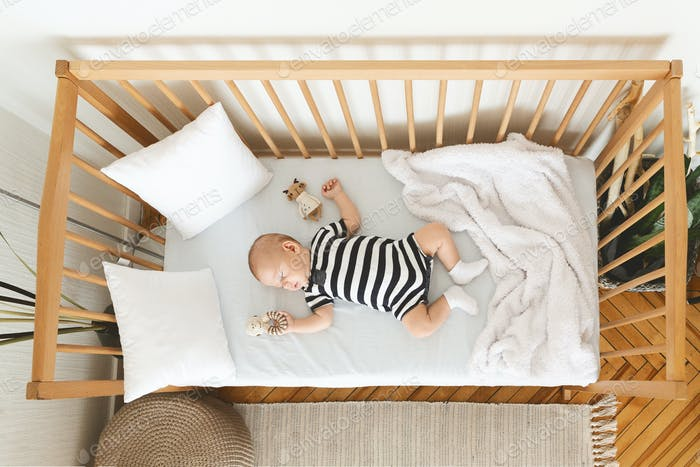 Adorable baby sleeping in crib with toy in his hand