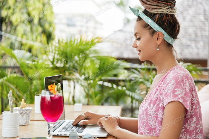 Fashionable female with dreadlocks hairstyle dressed casually, keyboards on laptop computer, searche