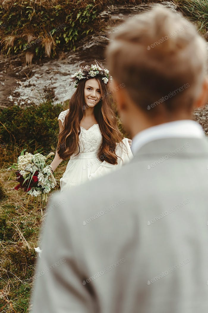 gorgeous bride and stylish groom looking at each other