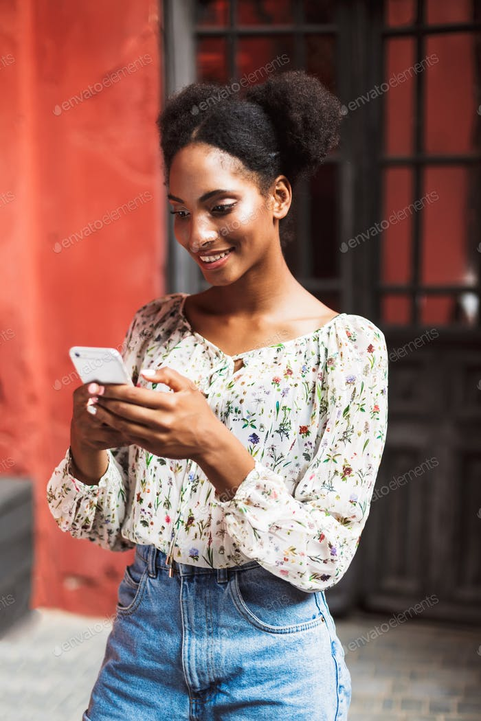 Pretty smiling african girl in blouse and denim skirt dreamily u