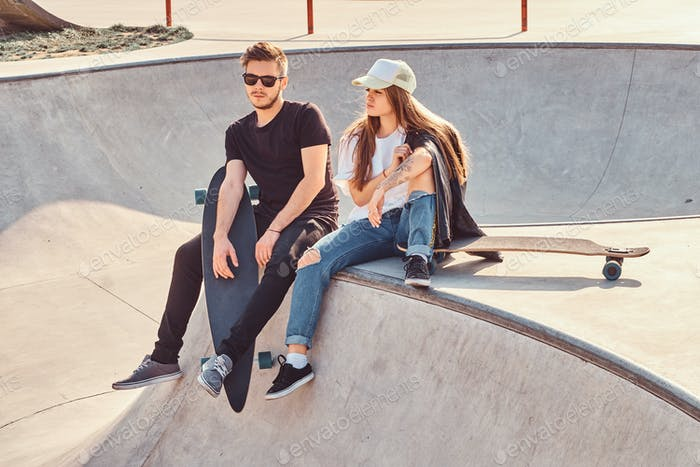 Young attractive couple of students are sitting at skatepark with their longboards