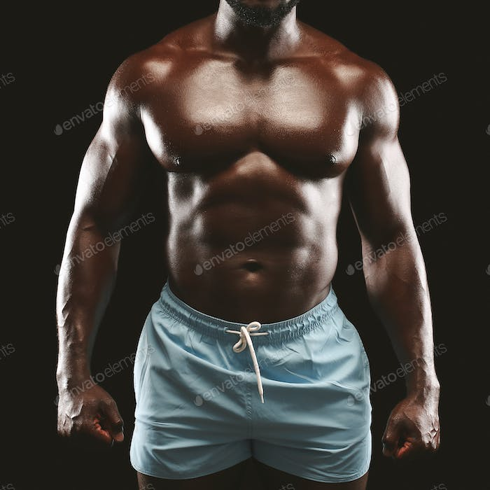 Strong athletic african guy demonstrating naked muscular body