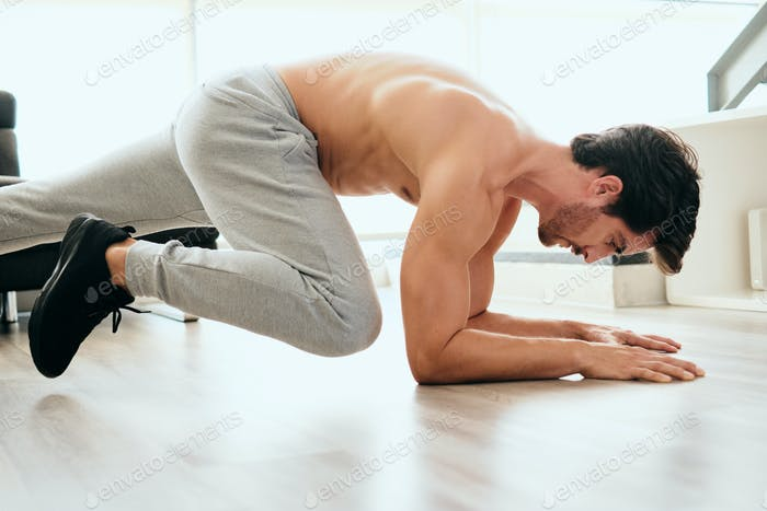 Adult Man Training ABS and Legs Doing Mountain Climbing Plank