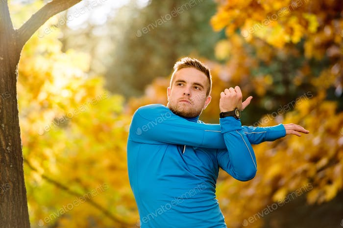 Young handsome hipster runner stretching outside in autumn natur