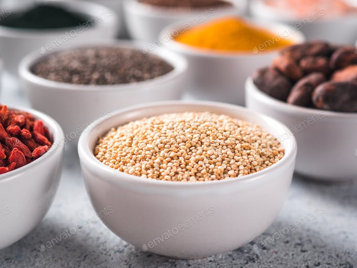 Quinoa grain in small white bowl and other superfoods