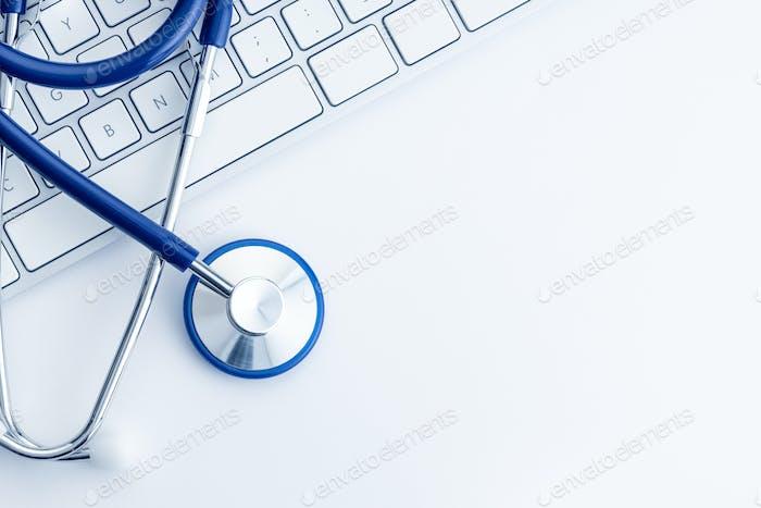 Stethoskop und Computertastatur auf weißem Schreibtisch